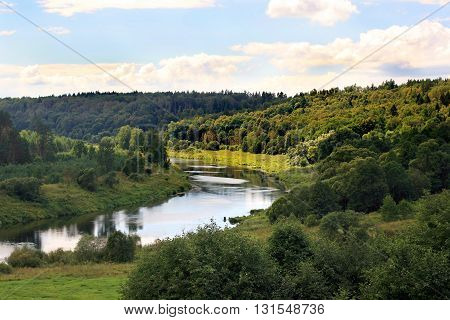 A clean river curve and a green forest around