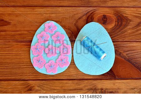 How to make a felt Easter egg. Sewing set Easter felt eggs. Felt details of egg, thread, needle on a brown wooden background