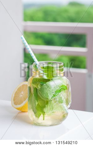 Tasty colorful drink with cold green tea mint and lemon in a glass jar on a white kitchen background closeup