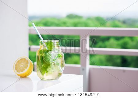 Tasty colorful drink with cold green tea mint and lemon in a glass jar on a white kitchen background horizontal with place for text