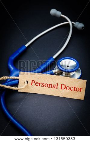 Personal doctor in paper tag with stethoscope on black background - health concept. Medical conceptual