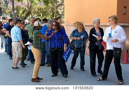 San Jose CA - May 26 2016: Unidentified participants waiting to enter Parkside Hall for the Hillary Clinton political rally are interviewed by radio broadcast journalist from station 94.1 KPFA.