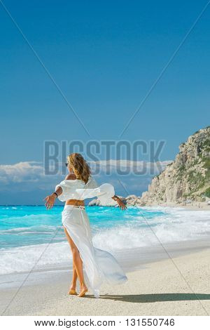 Beautiful young woman in white sarong walking  on the beach in Kefkada
