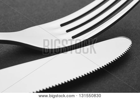 Knife and fork detail over a black background. Cutlery. Horizontal