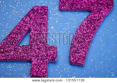 Number fortyseven purple color over a blue background. Anniversary. Horizontal