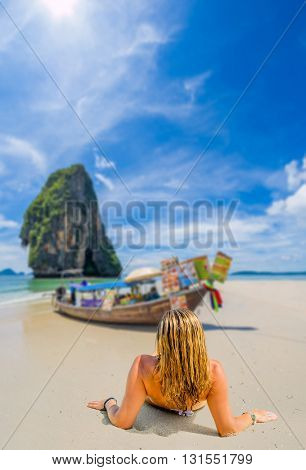 A sexy young woman  wearing a bikini and sun hat sitting on the beach in Krabi Thailand