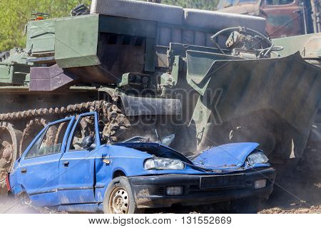 a heavy military tank crushes a blue car