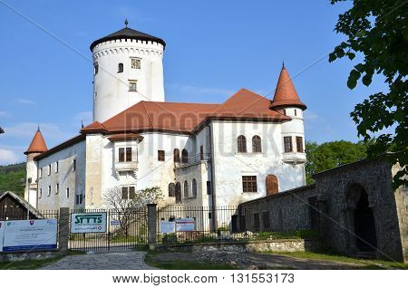 Zilina, Slovakia - May 20, 2016: Budatin Castle in sunshine in the evening view from castle park. On the fence hanging boards with information about reconstruction.