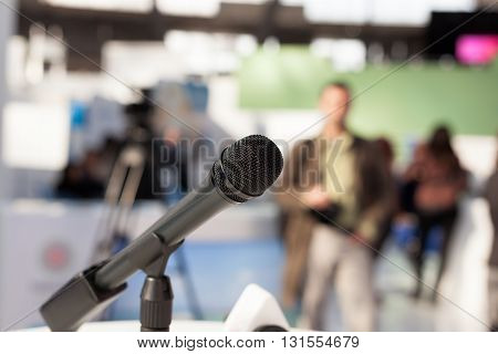 Microphone in focus against blurred audience during an media event