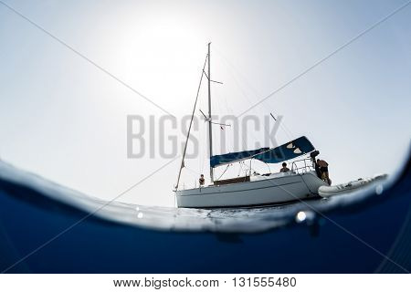 Split shot of the sail boat on surface and its underwater view