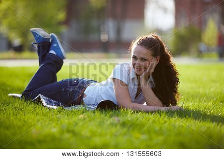Young beautiful woman is lying on a lawn