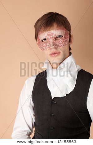 Portrait of a young gentlemen wearing dinner jacket and a mask. Shot in a studio.
