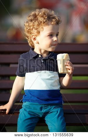 Little curly boy sits and eats ice-cream