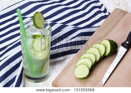 Summer cucumber cocktail, knife and sliced cucumbers on wooden desk.