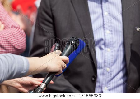 Press interview. Journalists holding microphones conducting  TV or radio interview