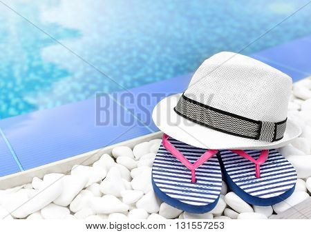 Flip-flops and hat at the pool on the white gravel.