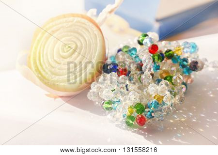 Half of onion and multicolour beads at sunny day