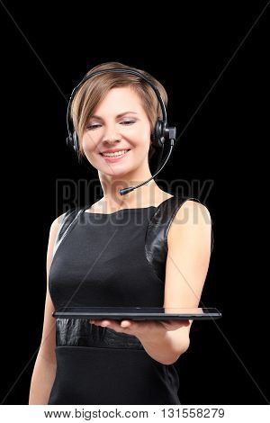 young brunette woman with a headset and a tablet on a Black background