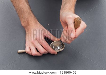 Man hands carving of a wooden spoon with hook knife on gray background
