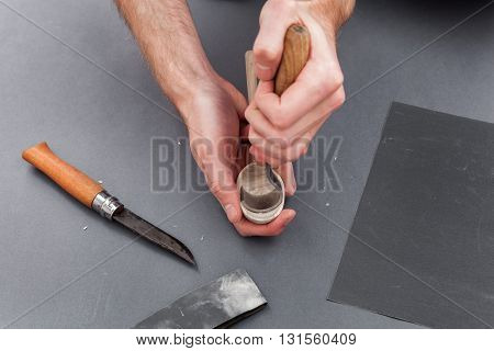 Man hands carving of a wooden spoon with hook knife on gray background with emery
