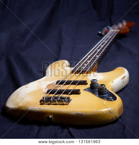 Old electric bass guitar focus on volume controller