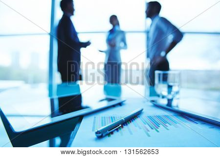 Close-up of business document and touchpad on the table with office workers in the background