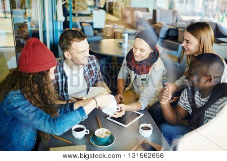 Group of friends sitting at cafe and drinking coffee