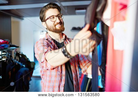 Handsome young man shopping for clothes at shop