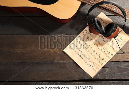 Guitar and music paper on wooden background