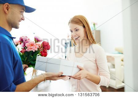 Delivery boy giving gift box and flowers to a surprised woman