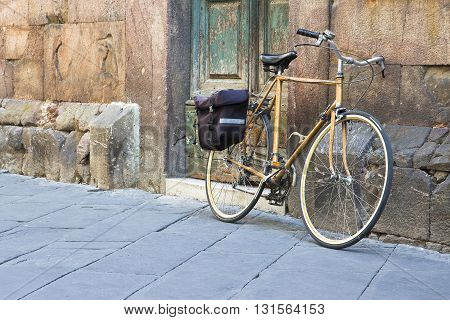 Yellow bicycle with bag against a stone wall in a street of a historic Tuscan center