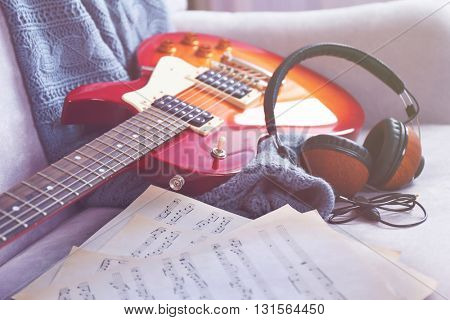 Electric guitar with notes and headphones on grey sofa