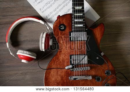 Brown electric guitar with headphones and notes on wooden background