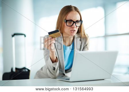 Angry businesswoman with credit card at laptop