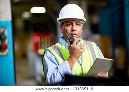 Engineer using walki talkie at factory