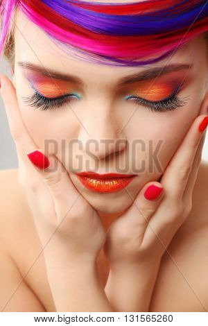Beautiful girl with colorful makeup, manicure and hairstyle