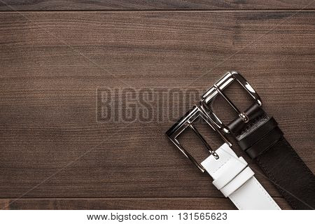 brown and white men's leather belts on wooden table