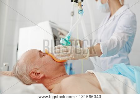 Doctor applying oxygen mask on senior patient