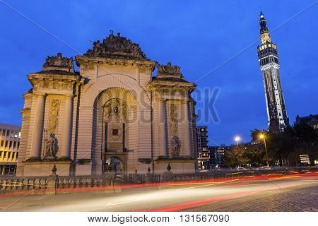 Paris Gate with Belfry of the Town Hall in the background in Lille in France in the evening