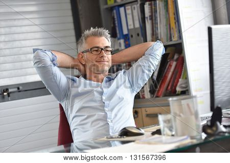 Businessman relaxing in front of desktop