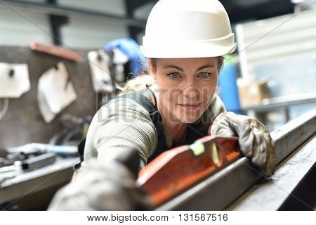 Metalworker with hardhat working on machine