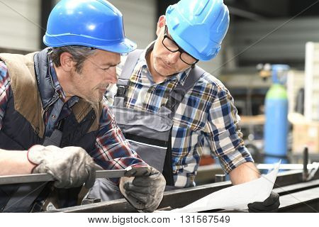 Engineers working on project in metallurgy workshop