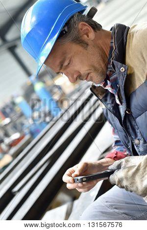 Man in steelwork factory using smartphone