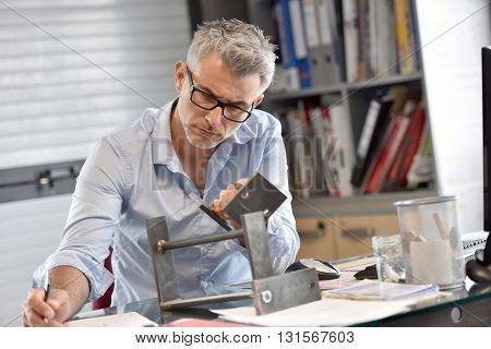 Industrial manager in office working on metal design