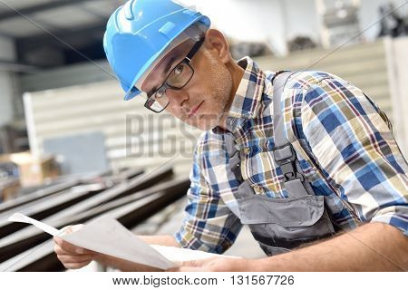Closeup of steelworks manager looking at plan