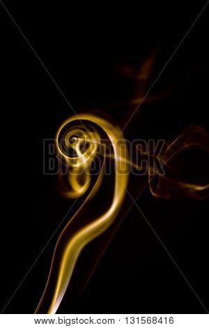 yellow Smoke spiral on black background closeup