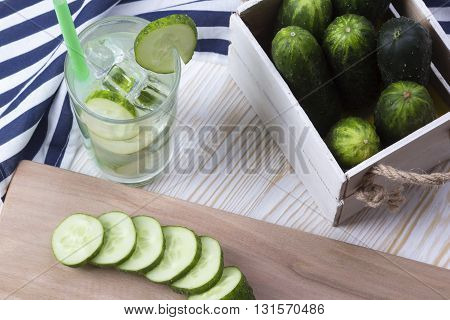 Summer cucumber cocktail and sliced cucumbers on wooden desk.
