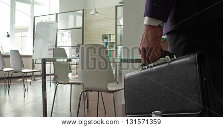 Businessman entering empty office with briefcase in hand