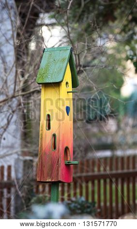 Bright birdhouse colored in green, yellow, red