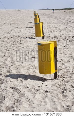 Garbage bins in a row on the beach in the Netherlands